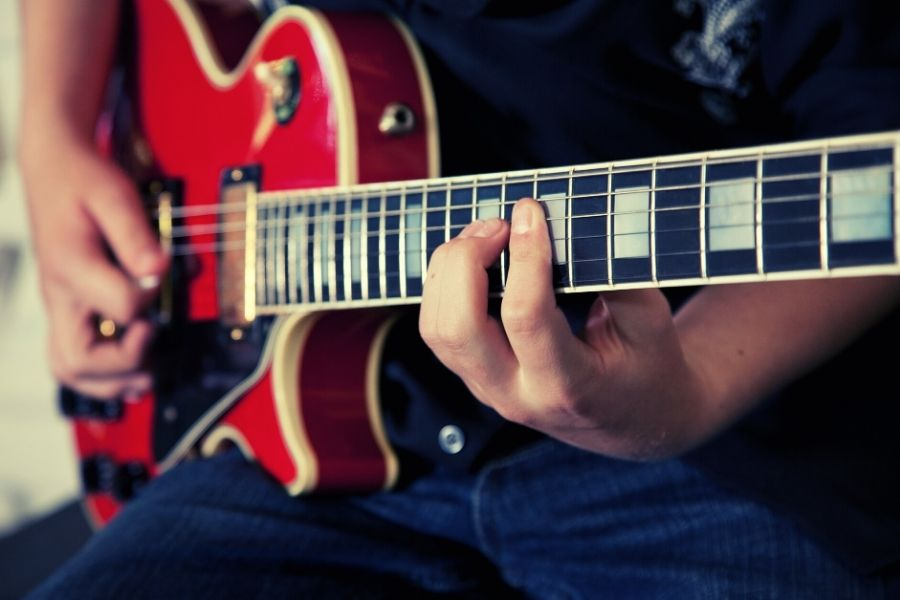 A person learning to play the guitar online.