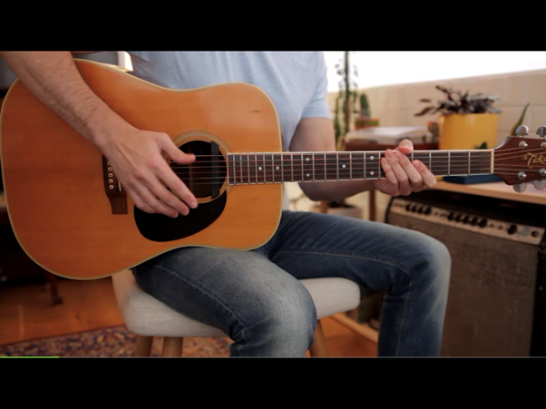 A person using Yousician to practice guitar.